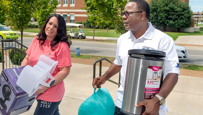 Sidney A. McPhee, MTSU president, helps Ginger Joslin move her daughter, Karli, into Corlew Hall.