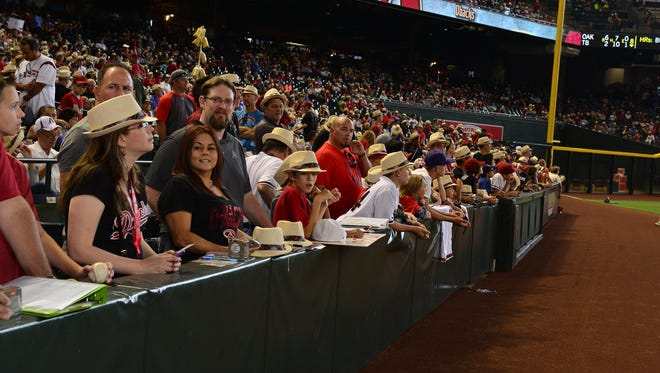 D-backs fans wait in line for autographs on May 24 with their D-Backs fedora, one of the most popular promotions this season.