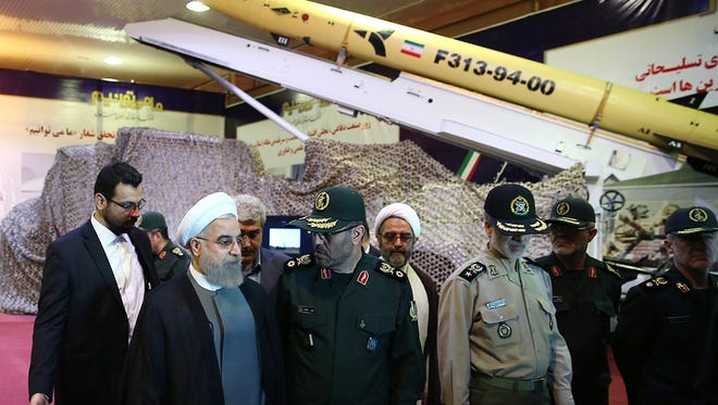 A handout picture released by the official website of the Iranian President Hassan Rouhani shows him (2nd L) and Defence Minister Hossein Dehghan (C) during the Defence Industry Day ceremony to unveil the country's latest domestically produced surface-to-surface Fateh (Winner) 313 missile in Tehran. The Fateh (Winner) 313 missile has a 500-kilometre (300 miles) range and features more advanced sensors and technology than earlier missiles, according to Sepah News, the website of Iran's powerful Revolutionary Guards.
