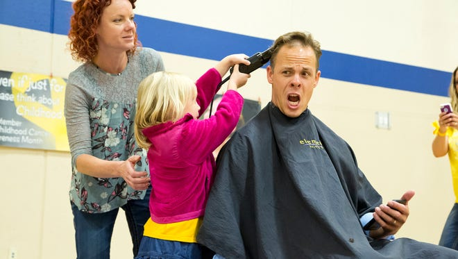 Principal Tony Ebeling at Bay Harbor Elementary School in Suamico bravely has his head shaved as part of Childhood Cancer Awareness activities.