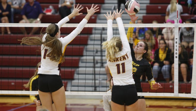 Southeast Polk's Carlee Beck spikes the ball past two Ankeny defenders during a match on Sept. 29 at Ankeny. Beck had 12 kills as the Rams won the match in four sets.