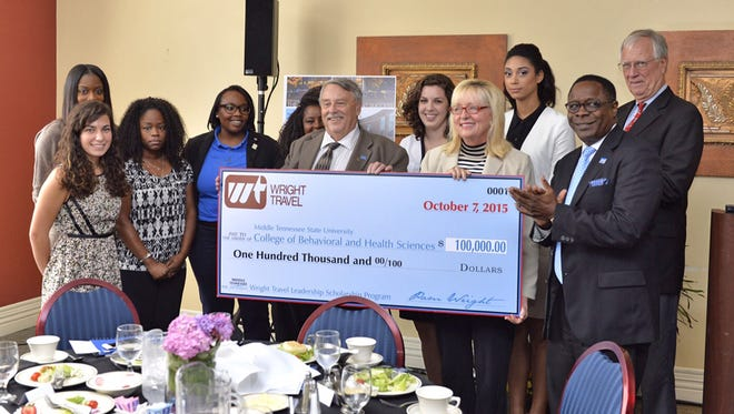 """Harold """"Terry"""" Whiteside, dean of the MTSU College of Behavioral and Health Sciences, center, accepts a $100,000 check from Pam Wright, center right, founder of Wright Travel, to start the Wright Travel Leadership Scholarship Program. Participants, from left, include, Mary Grace Farone, Tia Pride (partially hidden), Brittany Harris, Kamaria Cross, Faith Metcalf (partially hidden), Cambre Godwin, and Smatha Denby. At far right are MTSU President Sidney A. McPhee, front, and Scott Colclough, associate dean, College of Behavioral and Health Sciences, rear."""