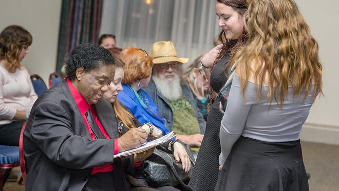 """Motown music icon Lamont Dozier, left, signs the paper liner for a vinyl copy of """"Motown: 25 #1 Hits from 25 Years"""" Wednesday, Oct. 21, for MTSU songwriting major Kayla Dunbar, center right, as her friend Heather Klein, a music business major, looks on. Seated next to Dozier is his wife, Barbara Dozier. Dozier was at MTSU for a special discussion about his 50-plus-year career and to be honored as the second Fellow of the Center for Popular Music at MTSU. (MTSU photo by J. Intintoli)"""