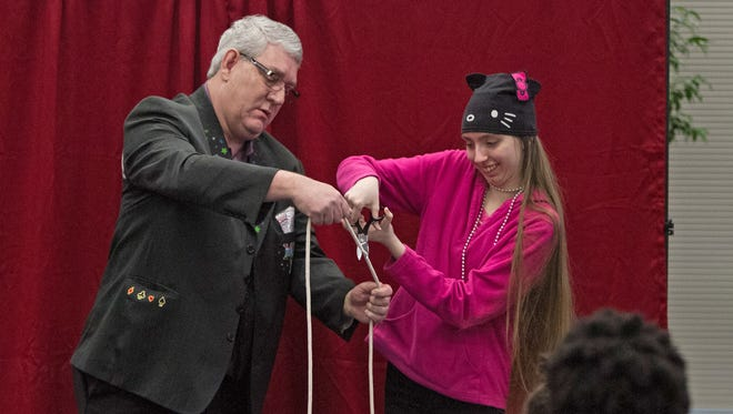 'Magic Man' David Scott is helped by Claire Fisher during a magic trick performed at the first-year celebration of the Amazing Abner Youth Magic Group that meets monthly at Linebaugh Library.