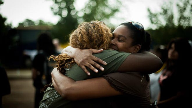 Two women embrace before leaving for a pilgrimage to Philadelphia, Miss., during the 2014 commemoration of Freedom Summer, led by the young women leaders of Southern Rural Black Women's Initiative.