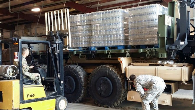 Louisiana National Guardsmen from the 1086th Transportation Company load and stack bottles of water to be delivered and distributed to affected parishes during emergency flood operations in Bunkie, Louisiana, March 13, 2016. The LANG has been assisting local officials in the flood fight since March 9.