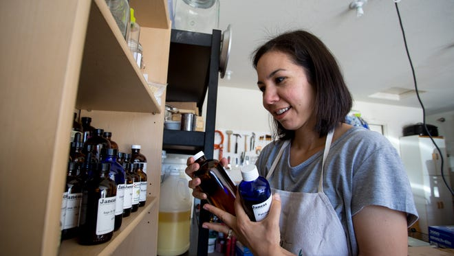 Jena Nagamine of Verano Bathery looks through the oils to find the ones used in the Soothe facial soap in her garage on Wednesday, Mar. 16, 2016 in Mesa, Ariz.