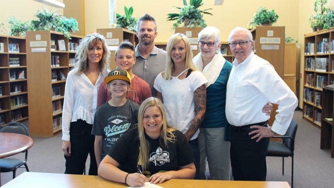 Valley Christian softball's Hailey Heeringa is surrounded by family as she signs her letter of intent to play at Dordt College in Iowa.