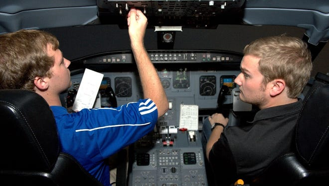 Kevin Allsop, left, and Charles Greenfield use a flight simulator after a Middle Tennessee State University dedication ceremony Thursday.