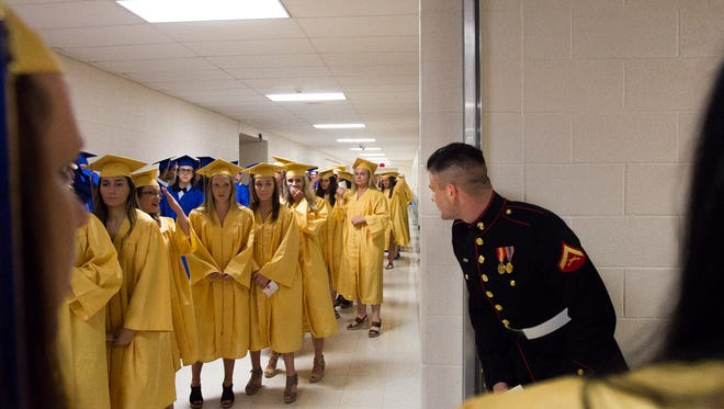 U.S. Marines Corporal Hunter Stokes looks around the corner in anticipation of surprising his brother, Connor, at the Kennard-Dale graduation commencement Friday. Stokes has been stationed on Okinawa, and the brothers had not seen each other in over two years.