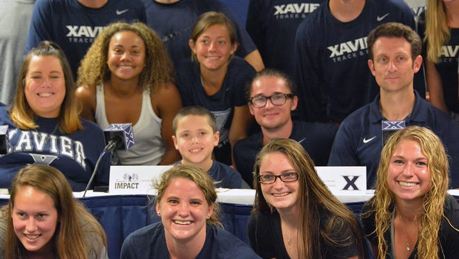 Florence second-grader Jacob Armstrong (center) is the newest member of Xavier's track and cross country teams. Armstrong, 7, has Cystic Fibrosis.