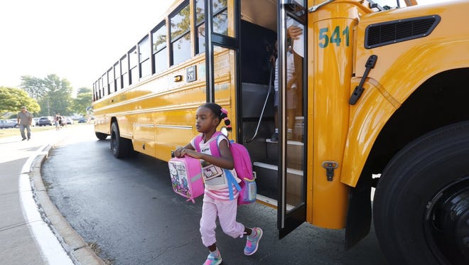 A student arrives at David Crane Elementary School, which is in the Rush-Henrietta Central School District, for the first day of school in 2016.