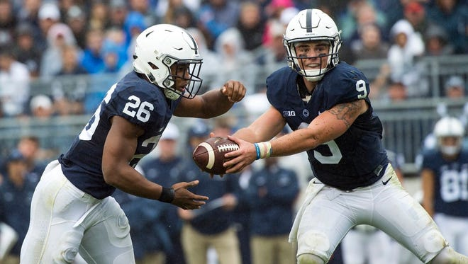 Penn State quarterback Trace McSorley, right, hands off the ball to running back Saquon Barkley during the Saturday's 38-14 win against Maryland.