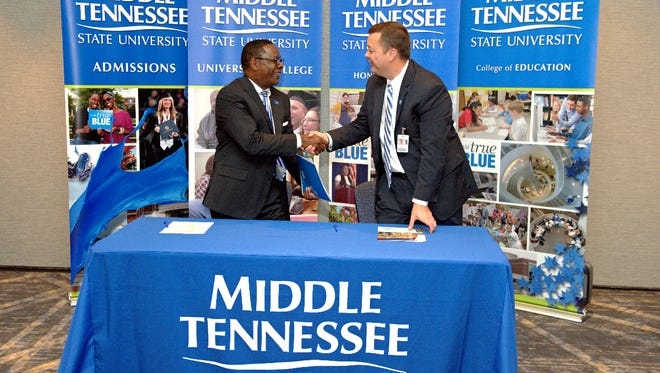 Middle Tennessee State University President Sidney McPhee, left, and Williamson County Schools' Assistant Superintendent of Secondary Schools Charles Farmer shake hands after expanding a dual enrollment program in 2015.