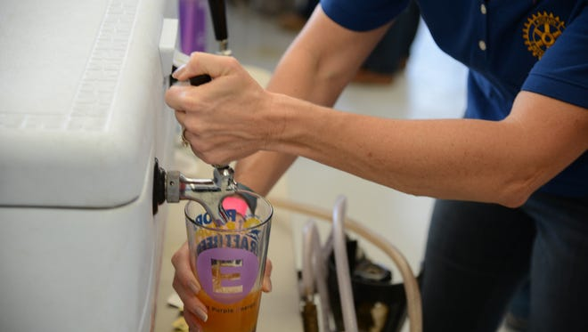 Pouring beer during last year's Props and Hops Craft Beer Festival. This year's is on Sat, Nov. 19 from 12 to 5 pm. $40 includes 8 four-ounce tastes. Live music, flight exhibitions, food vendors round out the fun for adults 21 years of age and older.