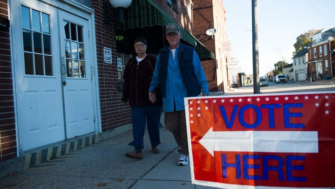 """Frank and Linda Bream, married 54 years, hold hands as they walk to go vote on Nov. 8. """"He's afraid I'll get away,"""" Linda Bream joked."""