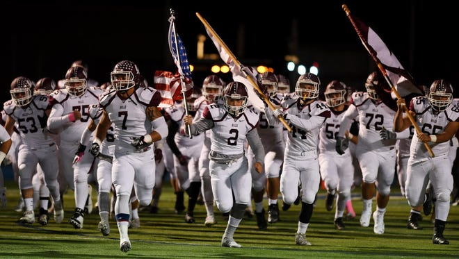 Wayne Hills takes the field before the start of the game last month.
