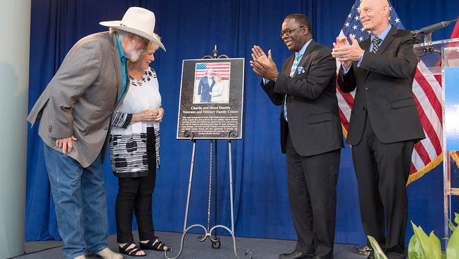Charlie and Hazel Daniels, left, view the MTSU plaque acknowledging their gifts and those from The Journey Home Project for the university's Charlie and Hazel Daniels Veterans and Military Family Center, named in their honor. Also celebrating the moment Aug. 23 are MTSU President Sidney A. McPhee, center right, and Keith M. Huber, senior adviser for veterans and leadership initiatives. The Daniels Family Center is located inside MTSU's Keathley University Center on campus. (MTSU photos by Andy Heidt)