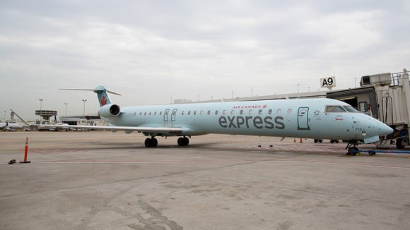 An Air Canada Express Bombardier CRJ-700 rests at the