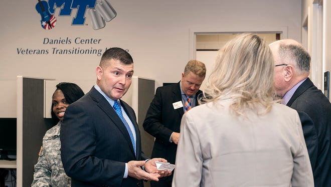 Shane Smith, left, swaps business cards with visitors from the corporate world attending the ribbon cutting for the Daniels Center Veterans Transitioning Home offices. Smith is interim employer search agent.