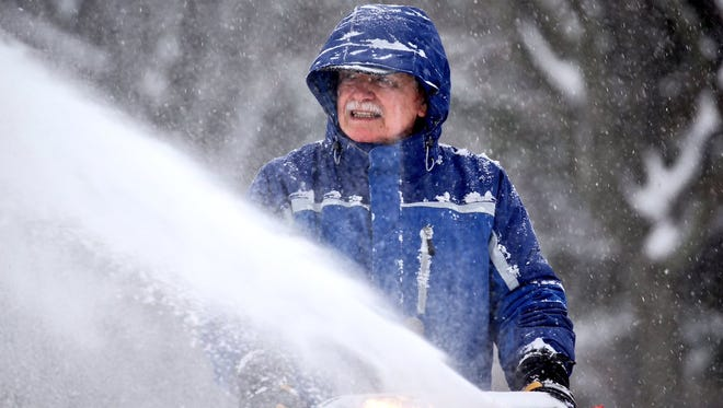 Bill Ernst tackles snow that's fallen in Irondequoit. He was without power for five days after the recent windstorm.