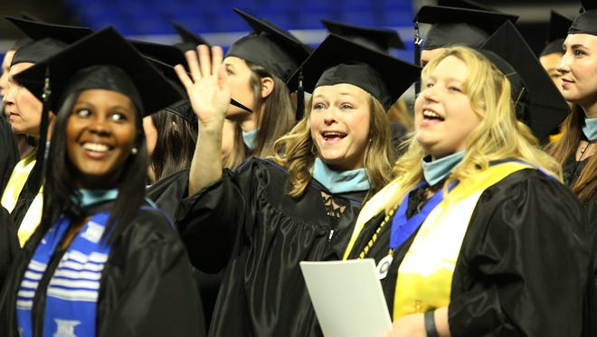 MTSU graduate students wave at loved ones cheering them on inside Murphy Center before the university's spring 2017 commencement ceremony for the College of Graduate Studies Friday, May 5. Two undergraduate commencement ceremonies are set Saturday, May 6.