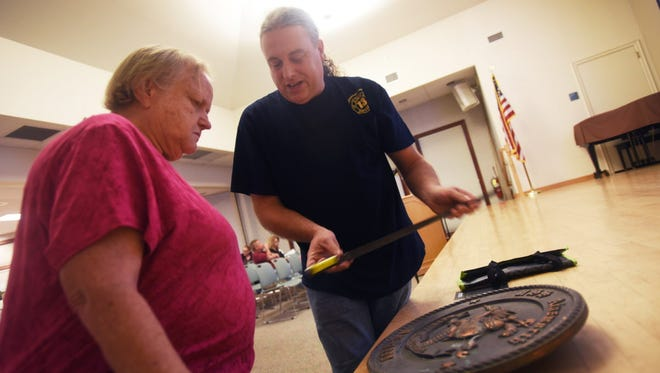 Cliff Ainsworth of Maywood, a ninth-generation descendent of the great grandson of Rebecca Nurse, who was hung in 1692 during the Salem Witch Trials, shares a Civil War bayonet, which he purchased from eBay, with Margaret Kaiser, president of the Genealogical Society, prior to a monthly meeting on July 24 at the Ridgewood Library.