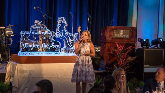 Claudine Léger-Wetzel, vice president of sales and marketing for Stock Development, started off an auction to raise money for Hurricane Irma victims during the Sand Dollar Awards.