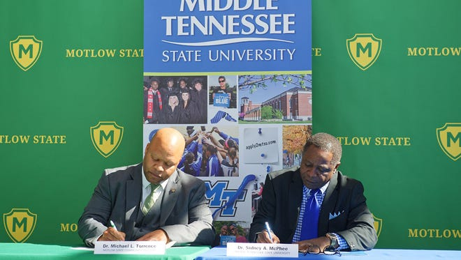 Motlow State Community College President Michael L. Torrence, left, and MTSU President Sidney A. McPhee sign the memorandum of understanding that will ease the transition of students transferring from the college to the university. The signing occurred May 1 in the Apple building on the Motlow campus in Smyrna, Tenn.