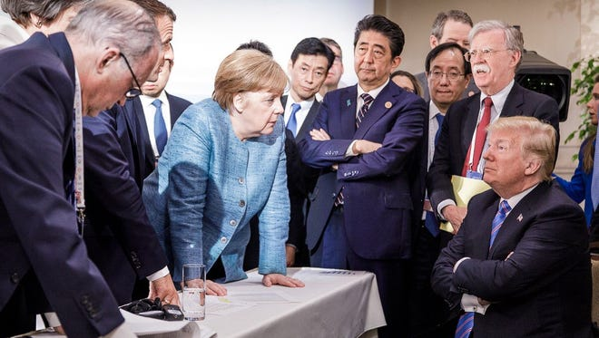 Photo released on Twitter by the German government shows President Donald Trump talking with German Chancellor Angela Merkel and other G-7 leaders.