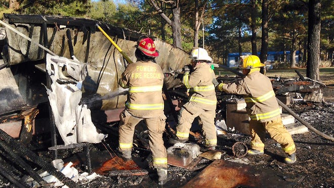 Powers VFD firefighter Mic Johnston, from left, Glade VFD Assistant Fire Chief Don Malson, and M&M firefighter Ashley Ward performing overhaul operations at a mobile home fire in Jones County Monday.