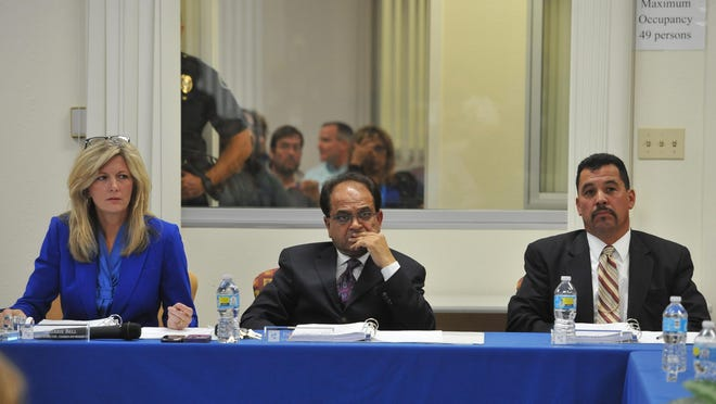 Tulare Regional Medical Center chairwoman Sherrie Bell, vice chairman Parmod Kumar and board member Richard Torrez listen to public comments during the TRMC board of directors meeting in the Allied Services building on Wednesday, April 27, 2016. The overflow crowd can be seen in an adjacent room.