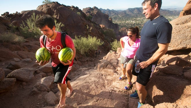 Chris Tomas (right) and Kelly Tomas, both of Minneapolis, Minn., watch as Jamie Trufin, 17, of Phoenix, hikes the Echo Canyon trail barefoot and carrying two watermelons up Camelback Mountain in Phoenix on Wednesday, November 19, 2014. For nearly the past six months Trufin has been hiking to the top of Camelback Mountain carrying watermelon and sharing it with other hikers on the summit.