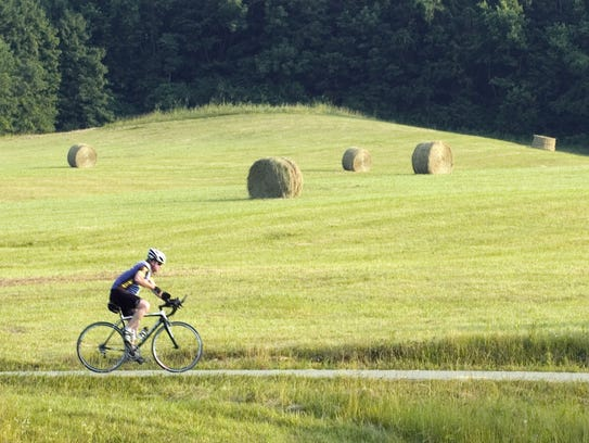 A lone cyclist rides on the Tri-County Triangle Trail
