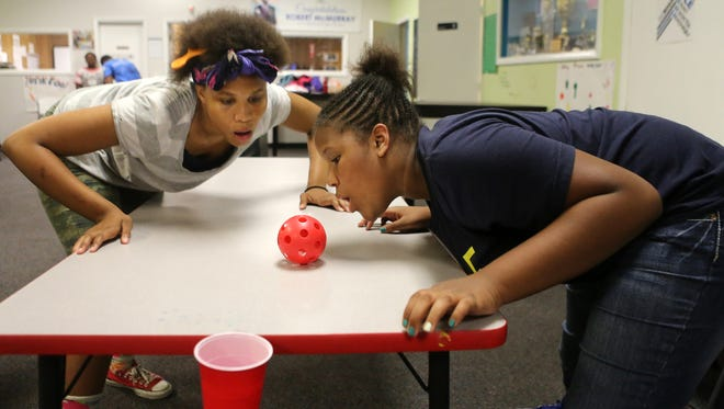 Raven Lumpkin (left) and Lamylia Lynch play a game together at the Boys and Girls Club in Price Hill. The club is moving to a larger facility four times its size on Glenway Avenue.