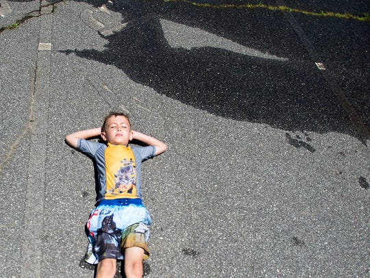 A student relaxes and dries off on the pavement Thursday