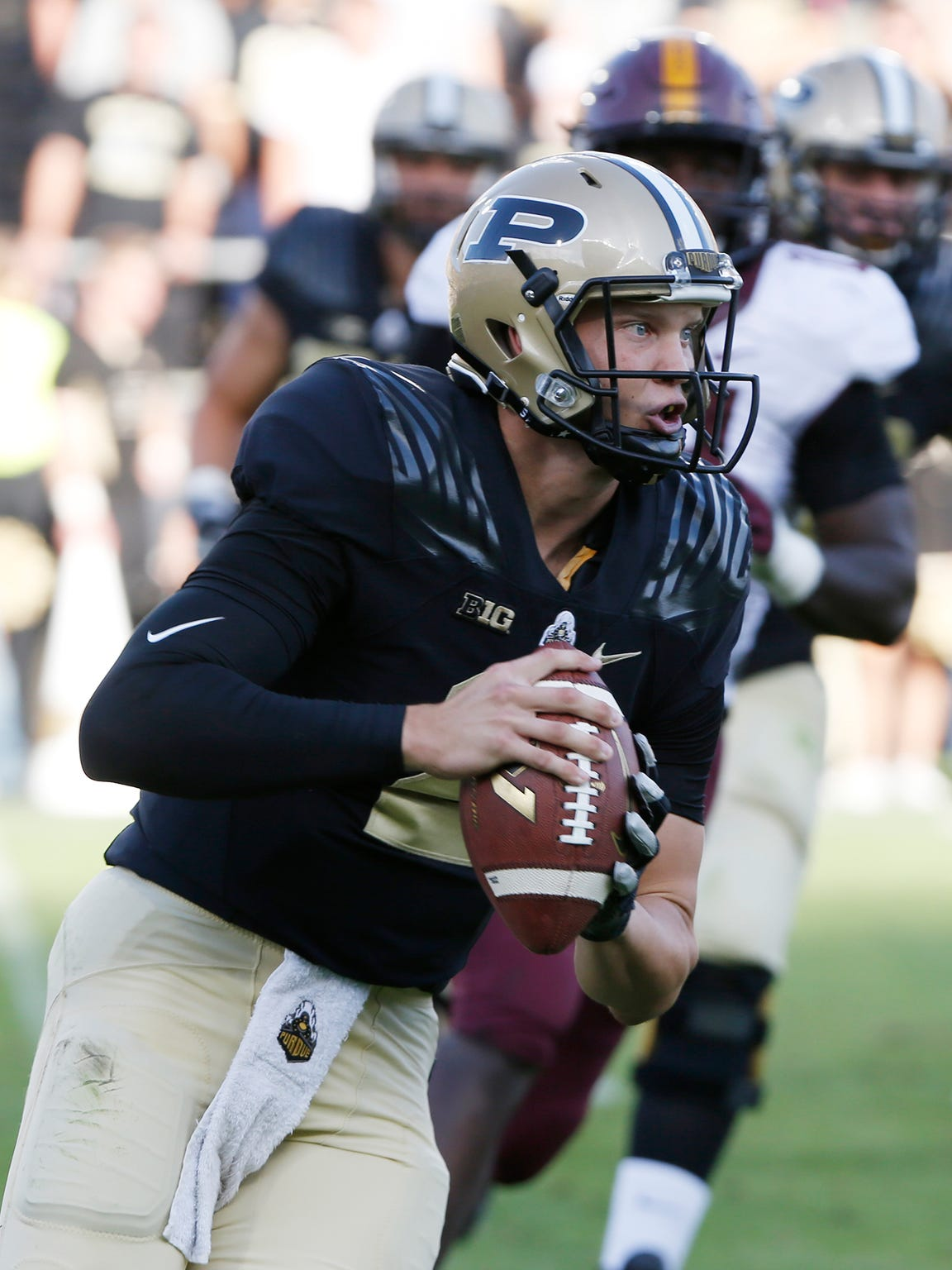 Purdue quarterback Elijah Sindelar rolls out to pass