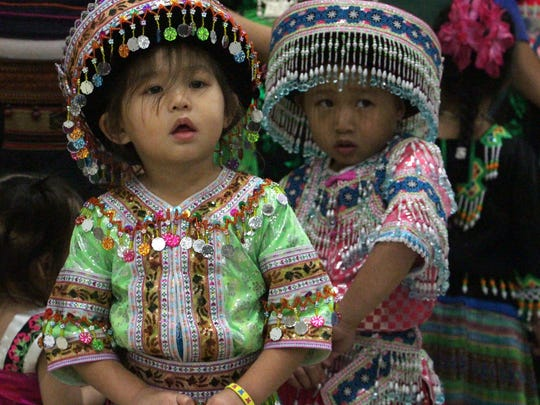 Sisters Trinity Chang, left, and Ava Chang of Wausau look on during a fashion show at a Hmong New Year celebration in 2012. Twenty years ago, a landmark magazine story asked whether Wausau could handle increased Hmong immigration.