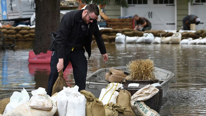 Ross Colyer, a Missoula City Police officer, loads sandbags into a boat to ferry across a flooded yard to build up a wall around a residence in Missoula, Mont., Friday, May 11, 2018. Montana rescuers pulled a man from raging floodwaters and authorities warned of dangerous debris being swept downstream as water levels continued rising Friday in rivers and streams across the western half of the state. (Kurt Wilson/The Missoulian via AP)