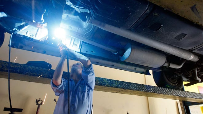 A mechanic works on replacing a catalytic converter.