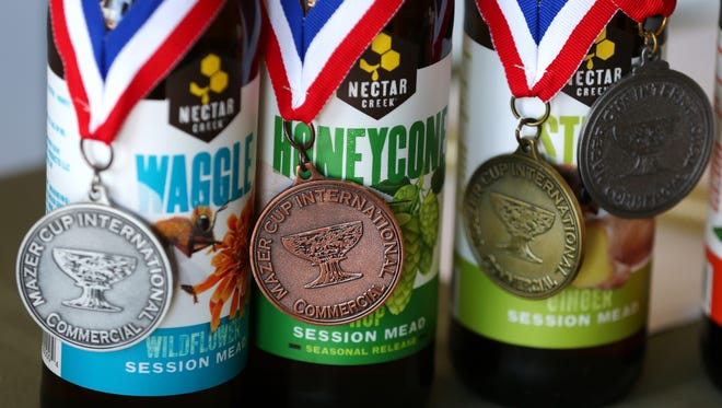 Medals from the Mazer Cup International mead competition hang on the winning bottles at Nectar Creek in Corvallis.