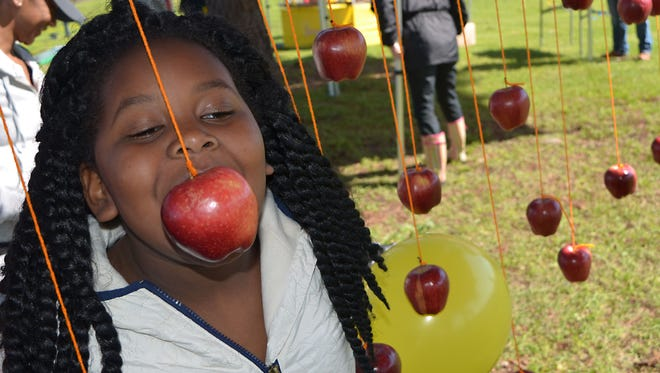 Quintasia Cavett, 7, of Jackson tries take a bite out of an apple during the 6th annual Sal & Mookie's Street Carnival held Saturday.
