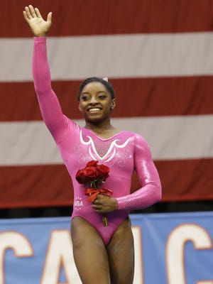 Simone Biles waves to the audience after winning the American Cup.