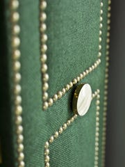 """In this undated photo, a closet door by Brian Patrick Flynn demonstrates the designer's love of turning contractor grade materials into high design with the addition of fabric, satin brass pulls and perimeter outlines with brass nailheads. Flynn says, """"Although it may seem small, hardware can make the biggest impact of all elements in a space."""" (Sarah Dorio/Brian Patrick Flynn via AP)"""