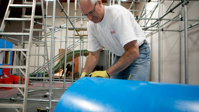Vice-president and installer for KidSteam Greg Kazel works on installing a piece of equipment at the Blu Play Cafe in Wisconsin Rapids, Tuesday, Oct. 13, 2015. KidSteam is a commercial indoor playground equipment company.