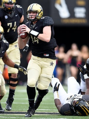 Vanderbilt quarterback Kyle Shurmur (14) scrambles out of the pocket to throw a pass against Missouri on Saturday.