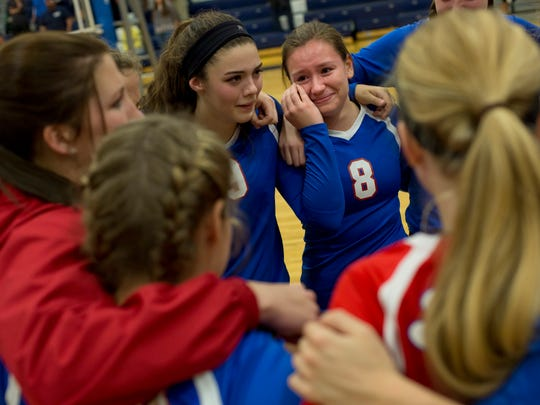 St. Clair senior Michaela Buckley smiles and wipes away a tear as she stands in a huddle with teammates after losing to Marysville in a district volleyball game Thursday, November 5, 2015 at Algonac High School.