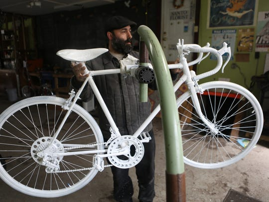 A ghost bike for Michael Prater awaits its final coat of paint Tuesday at Mobo Bicycle Cooperative in Northside. The practice of placing a bicycle painted white where a cyclist was killed serves to memorialize the person as well as remind motorists to share the road.
