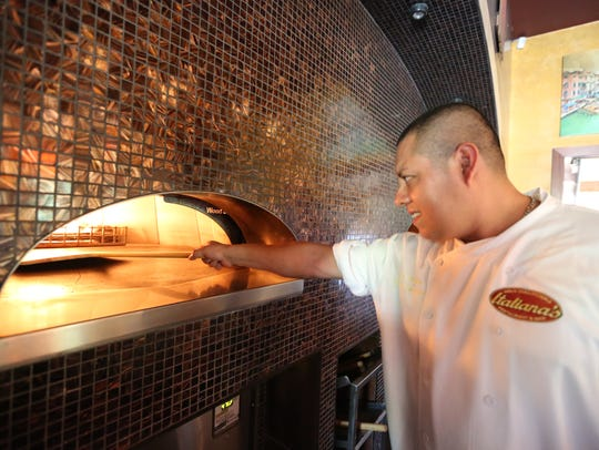 Omar Reyes of Suffern checks on the pizza oven at Italiana's