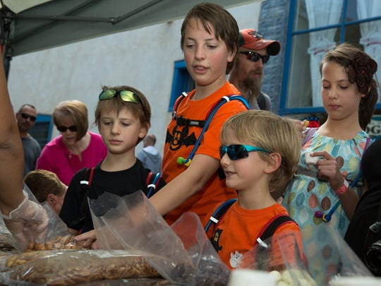 Eight-year-old Josh Jones, left, along with his siblings Jaiden, 14, Justin, 7, and Shaylynn, 12, choose free samples of coated treats from the Mesilla Valley Store on Saturday, October 8, 2016, during Mesilla's First Annual Pecan Festival.